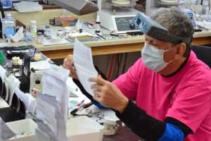 Quality dental lab - dental laboratory technician reading a prescription slip